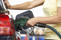 Woman putting gas in car